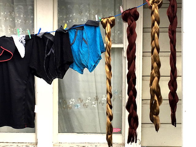 A washing line with shorts and long braids.