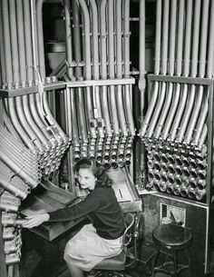 Young woman working a pneumatic tube cash carrier at Marshalls department store, date unknown, public domain
