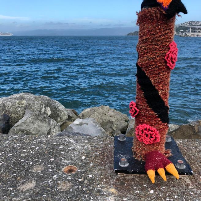 Harbourside post wrapped in colourful knitting, with bird foot. Ferry sailing in the distance.