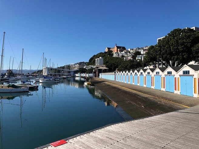 Photo of blue boat houses, calm water, yachts, houses on a hill
